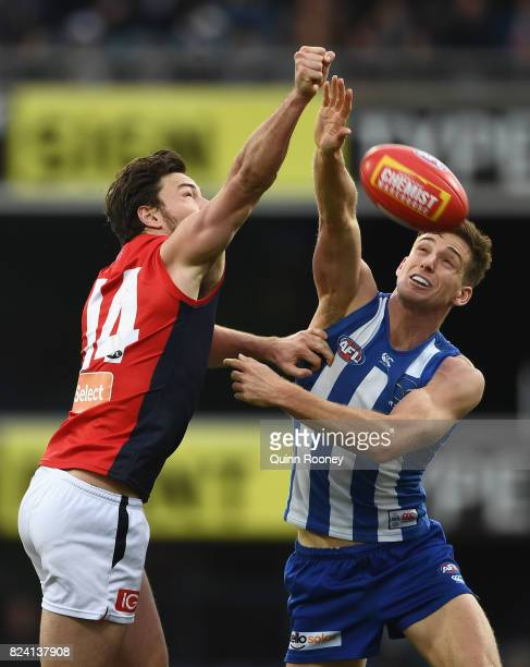 Michael Hibberd of the Demons and Shaun Atley of the Kangaroos compete for the ball during the round 19 AFL match between the North Melbourne...