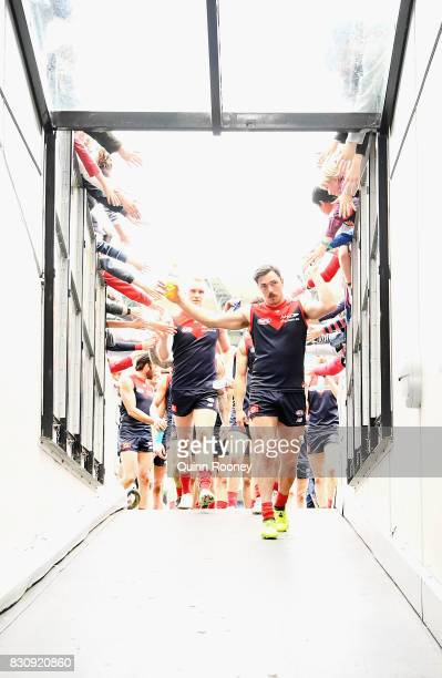 Michael Hibberd of the Demons high fives fans after winning the round 21 AFL match between the Melbourne Demons and the St Kilda Saints at Melbourne...