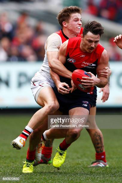 Michael Hibberd of the Demons is tackled by Jack Billings of the Saints during the round 21 AFL match between the Melbourne Demons and the St Kilda...