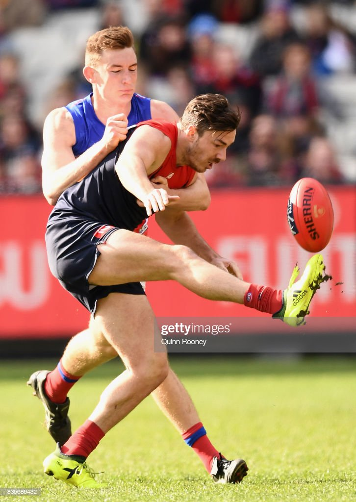 Michael Hibberd of the Demons kicks whilst being tackled by Harris Andrews of the Lions during the round 22 AFL match between the Melbourne Demons and the Brisbane Lions at Melbourne Cricket Ground on August 20, 2017 in Melbourne, Australia.
