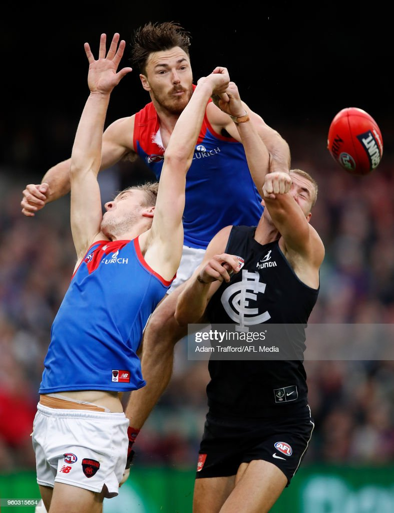 Michael Hibberd of the Demons (top) punches the ball away from Oscar McDonald of the Demons and Harry McKay of the Blues during the 2018 AFL round nine match between the Carlton Blues and the Melbourne Demons at the Melbourne Cricket Ground on May 20, 2018 in Melbourne, Australia.