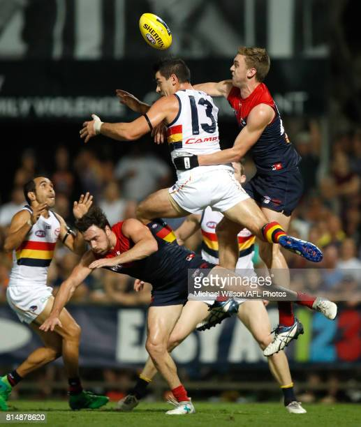 Michael Hibberd of the Demons, Taylor Walker of the Crows and Oscar McDonald of the Demons compete for the ball during the 2017 AFL round 17 match...