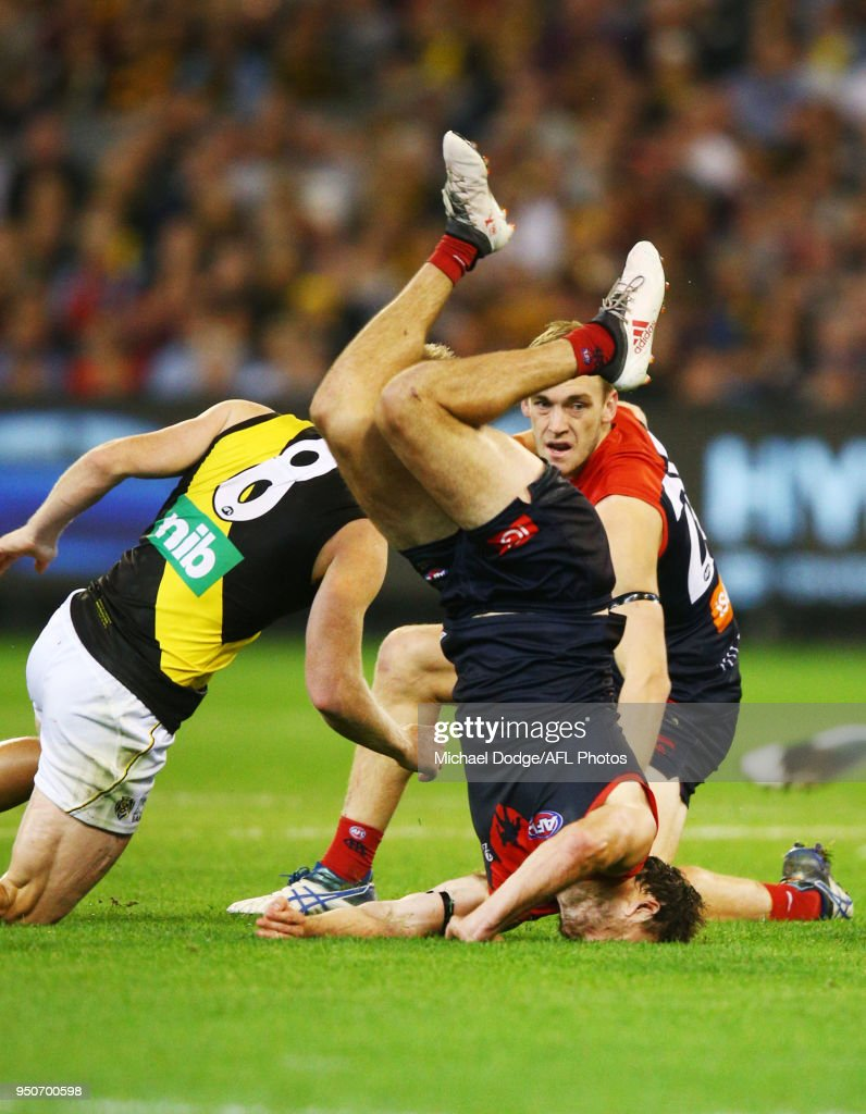Michael Hibberd of the Demons tumbles over Jack Riewoldt of the Tigers during the 2018 AFL round five match between the Melbourne Demons and the Richmond Tigers at the Melbourne Cricket Ground at Melbourne Cricket Ground on April 24, 2018 in Melbourne, Australia.