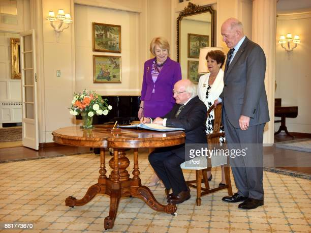 Michael Higgins President of Ireland signs the visitors book attended by Sabina Higgins Lady Lynne Cosgrove and Governor General Peter Cosgrove...