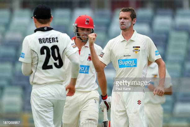 Michael Hogan of the Warriors celebrates the wicket of Sam Raphael of the Redbacks during day one of the Sheffield Shield match between the Western...