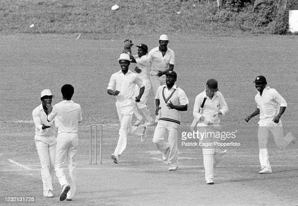 Michael Holding of West Indies celebrates his 100th Test wicket with teammate Desmond Haynes after England batsman Brian Rose is caught behind for 5...