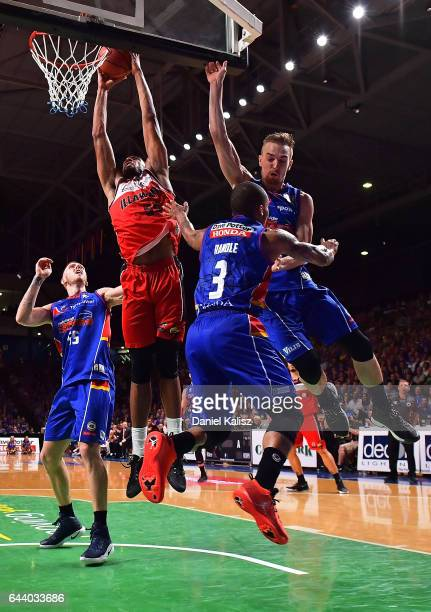 Michael Holyfield of the Illawarra Hawks dunks over Jerome Randle and Anthony Drmic of the Adelaide 36ers during game three of the NBL Semi Final...