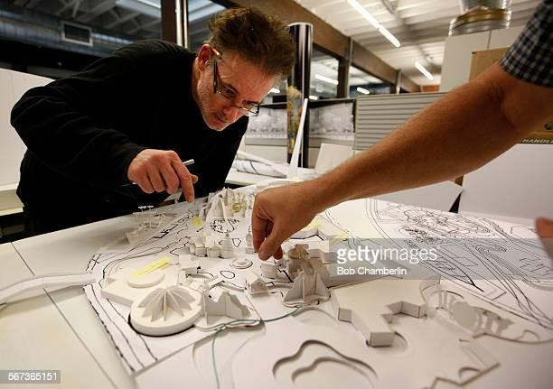 Michael Hood left watches as Bob Baranick right adjusts a tiny building on an amusement park model at Gary Goddard Entertainment in their North...