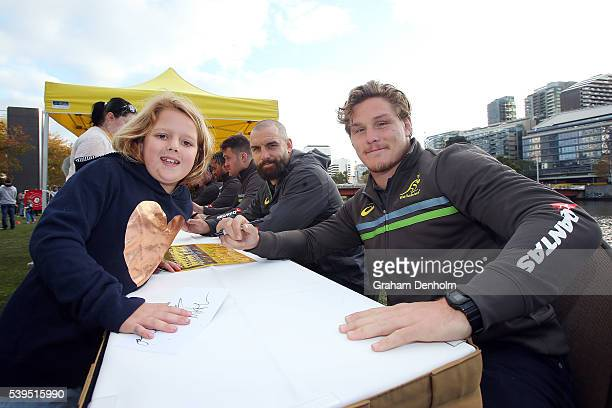 Michael Hooper and Scott Fardy of the Wallabies pose for a photograph with a young fan during the Australian Wallabies Fan Day at The Crown Promenade...