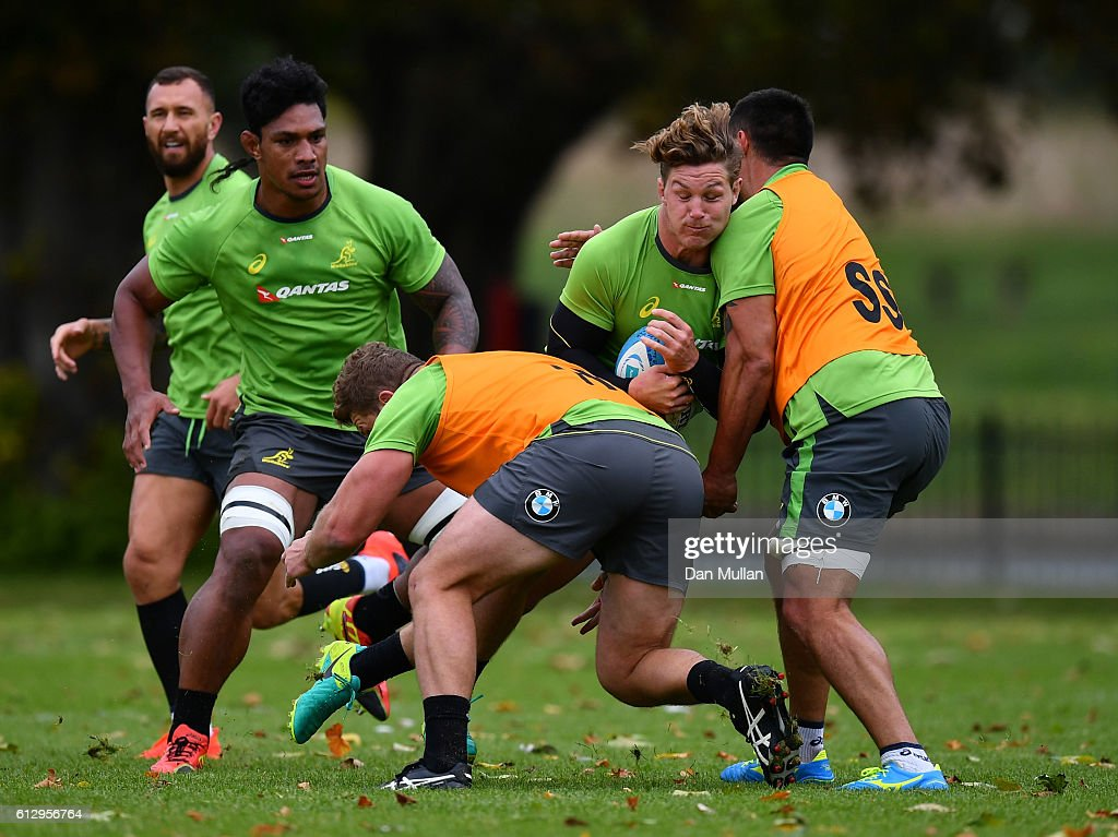 Michael Hooper of Australia is tackled by James Slipper and Leroy Houston of Australia during an Australia training session at The Lensbury Hotel on October 6, 2016 in London, United Kingdom.