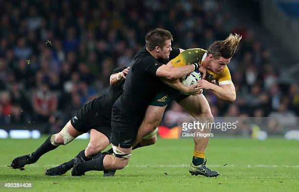 Michael Hooper of Australia is tackled by Richie McCaw of New Zealand during the 2015 Rugby World Cup Final match between New Zealand and Australia...