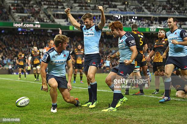 Michael Hooper of the Waratahs celebrates with his team mates Rob Horne Andrew Kellaway and Matt Carraro of the Waratahs after scoring a try during...