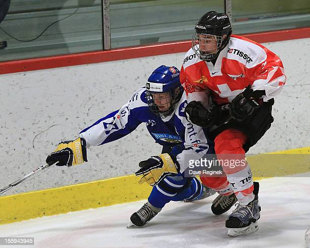 Michael Hugli of Switzerland battles in the corner with Erik Autio of Finland during the U-18 Four Nations Cup tournament on November 9, 2012 at the...