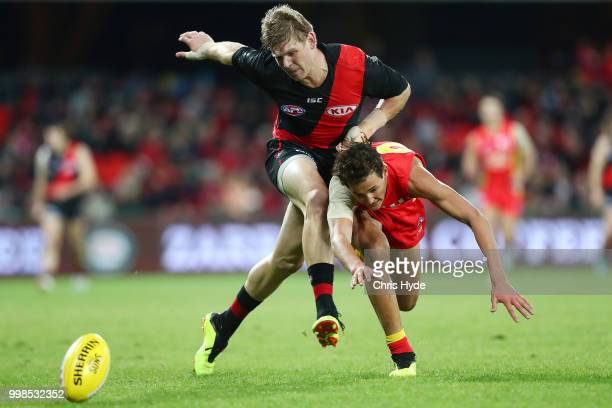 Michael Hurley of the Bombers and Wil Powell of the Suns compete for the ball during the round 17 AFL match between the Gold Coast Suns and the...