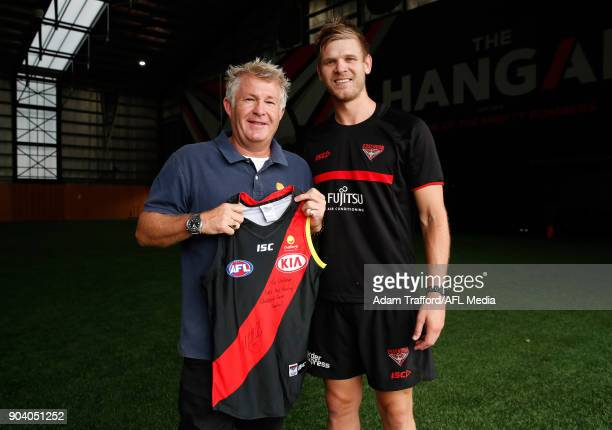 Michael Hurley of the Bombers poses for a photo with David Rogers CEO of Challenge after presenting him with a jumper from the 2017 Clash for Cancer...