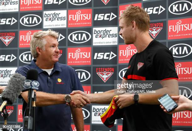 Michael Hurley of the Bombers presents with David Rogers CEO of Challenge with a jumper from the 2017 Clash for Cancer match during the Essendon...