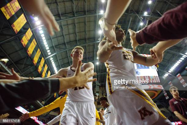 Michael Hurt and Reggie Lynch of the Minnesota Golden Gophers celebrate a win against the USC Upstate Spartans with fans after the game on November...