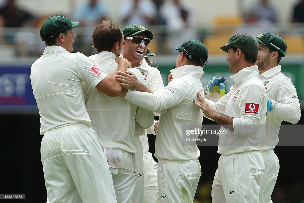 Michael Hussey of Australia celebrate catching Alviro Petersen of South Africa during day one of the First Test match between Australia and South Africa at The Gabba on November 9, 2012 in Brisbane, Australia.