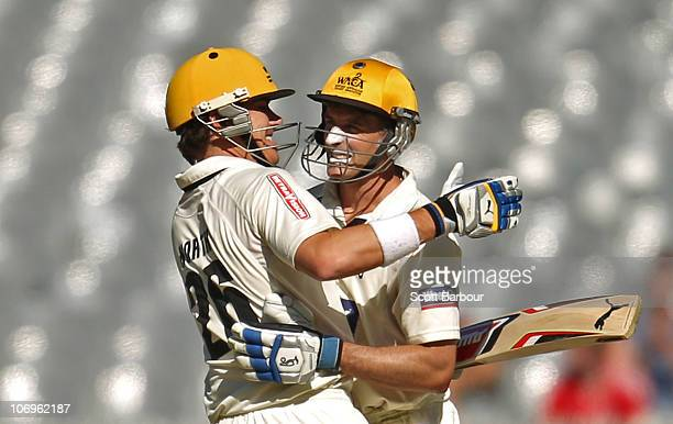 Michael Hussey of the Warriors is embraced by team mate Marcus North after reaching his century during day three of the Sheffield Shield match...