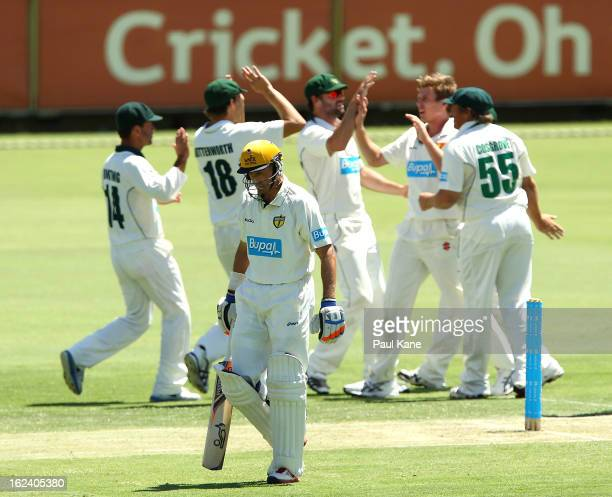 Michael Hussey of the Warriors walks from the field as James Faulkner of the Tigers celebrates with team mates during day three of the Sheffield...