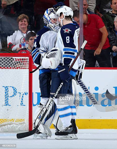 Michael Hutchinson of the Winnipeg Jets is congratulated by teammate Jacob Trouba after the 31 win over the New Jersey Devils on October 9 2015 at...