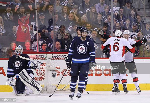 Michael Hutchinson of the Winnipeg Jets looks on as Alex Chiasson of the Ottawa Senators celebrates a goal by Bobby Ryan in secondperiod action in an...