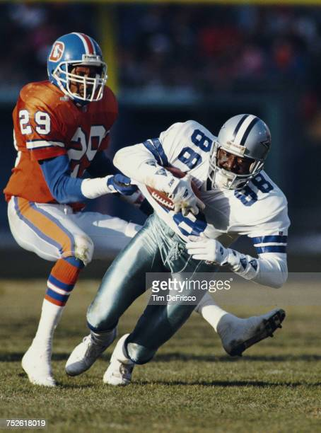 Michael Irvin wide receiver for the Dallas Cowboys is partially tackled by Charles Dimry defensive back for the Denver Broncos during their National...