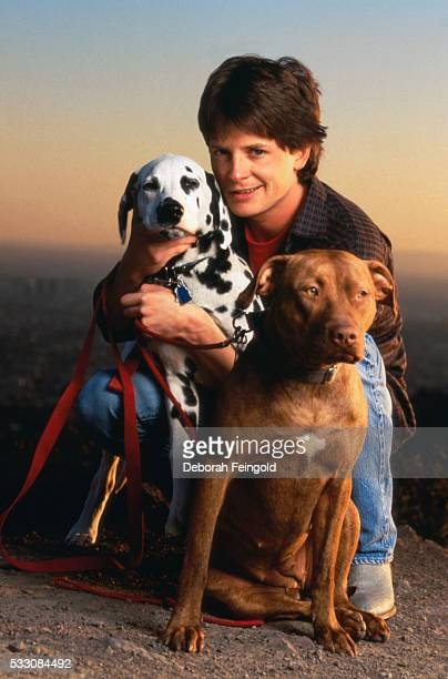Michael J Fox Crouching with Two Dogs
