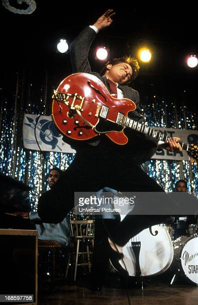 Michael J Fox leaping in air with guitar in a scene from the film 'Back To The Future' 1985