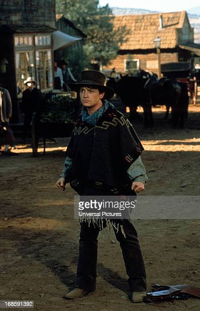 Michael J Fox standing in the dirt wearing a poncho in a scene from the film 'Back to the Future Part III' 1990