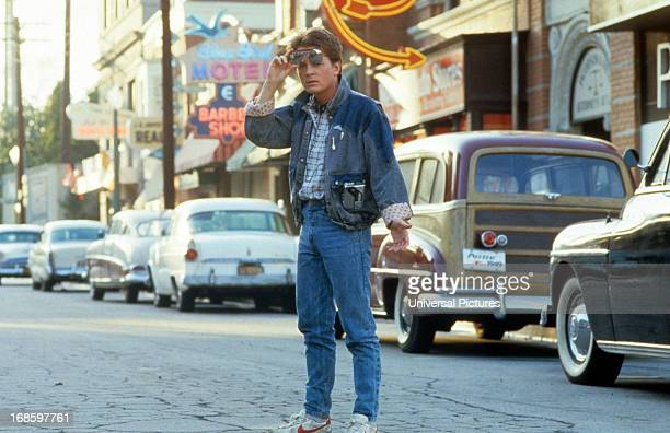 Michael J Fox walking across the street in a scene from the film 'Back To The Future' 1985