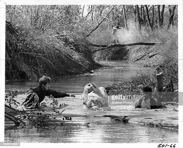 Michael J Pollard Faye Dunaway and Warren Beatty attempt to cross a creek in a scene from the film 'Bonnie And Clyde' 1967