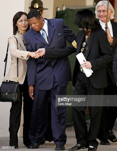 Michael Jackson and attorney Susan Yu shake hands with as his security guard walks through following jury selection in Jackson's child molestation...