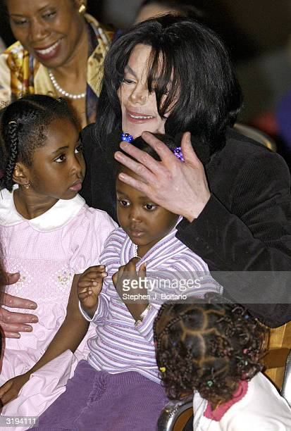 Michael Jackson embraces children onstage who performed for him at the Ethiopian Embassy on April 1 2004 in Washington DC before receiving the...