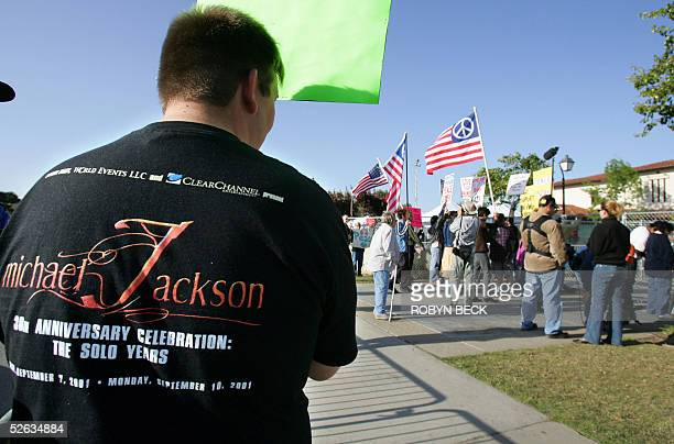 Michael Jackson fan BJ Hickman watches as a group of local antiwar protestors attract media attention at the prime fan spot outside the fence...