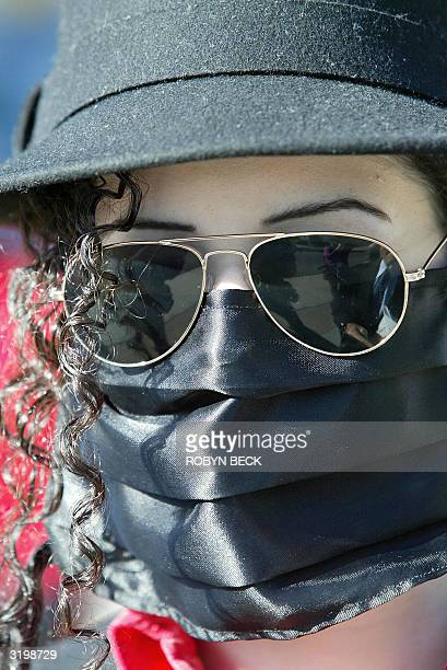 Michael Jackson fan Diana Enola of Matick Massachusetts wears a Jacksonstyle black face mask and hat as a sign of support for the pop star outside...