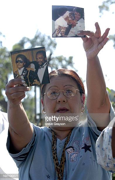 A Michael Jackson fan holds a cover of Jackson's album Thriller outside the gates Michael Jackson's Neverland Ranch in Los Olivos California after...
