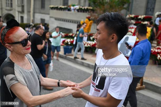 Michael Jackson fan Michael Liang a student visiting from Beijing China comforts fellow fan Carla Michael from Italy as supporters remember the King...
