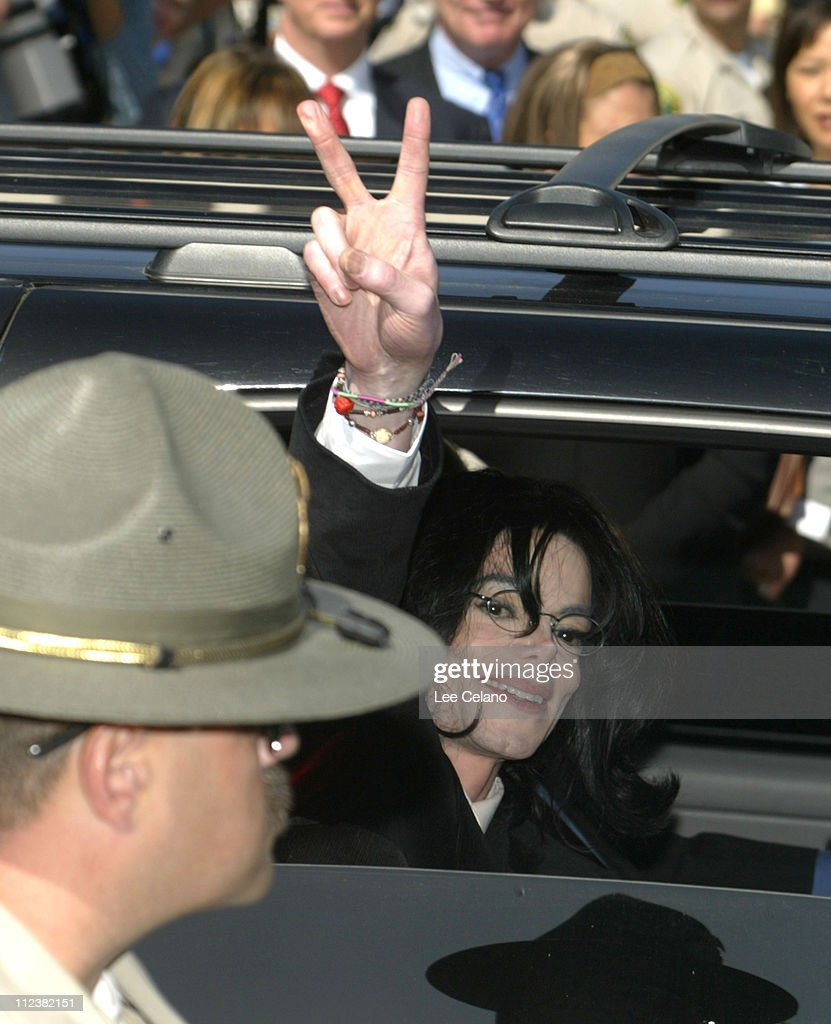 Michael Jackson gives the peace sign as he leaves during his indictment on charges related to child molestation at the courthouse in Santa Maria, Calif., Friday April 30, 2004