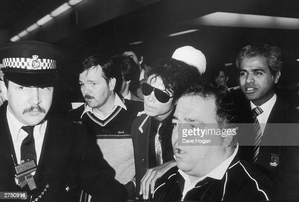 Michael Jackson is lead through a crowd by policeman on a promotionial tour of Great Britain in London