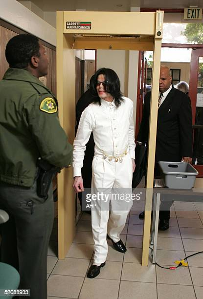 Michael Jackson is screened by sheriff's deputies as he enters the Santa Barbara County Courthouse for jury selection in his child molestation trial...