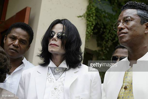 Michael Jackson is surrounded by brothers Jackie Jackson and Jermaine Jackson after court on September 17 2004 in Santa Maria California