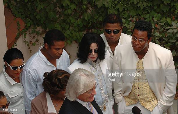 Michael Jackson is surrounded by family as they listen to attorney Thomas Mesereau Jr speak to the media outside the Santa Maira courthouse on...