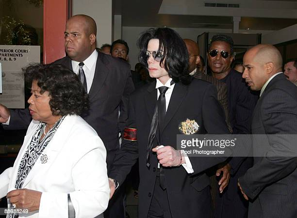 Michael Jackson leaves Santa Barbara County Courthouse clutching a tissue and his mother Katherine Jackson's arm after a jury acquitted on all counts...