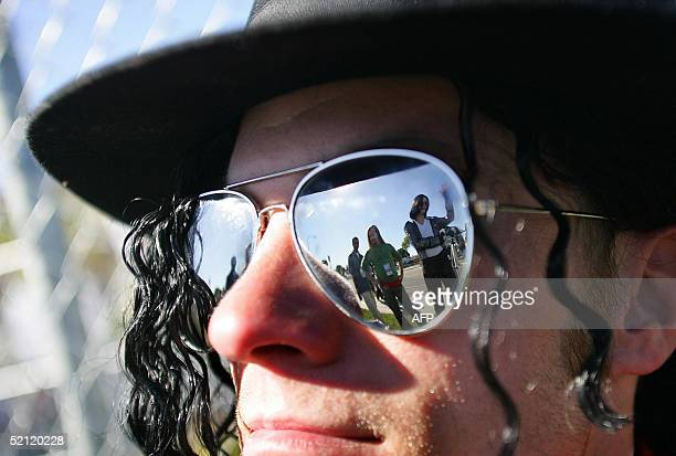 Michael Jackson lookalike Pete Carter is reflected in the glasses of Sean Vezina another Jackson lookalike as they wait outside Santa Barbara County...