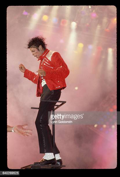 Michael Jackson on stage performing He is shown fulllength on a colorfully lit stage wearing a red leather jacket and sequined socks Photograph 1984