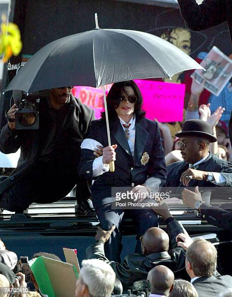 Michael Jackson sits on top of his SUV as he acknowledges hundreds of fans gathered outside the Santa Maria Courthouse during the Michael Jackson...