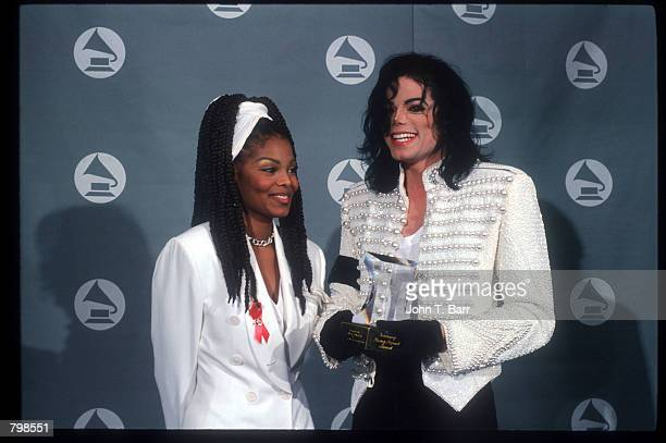 Michael Jackson smiles with his sister Janet Jackson at the Grammy Awards February 26 1993 in Los Angeles CA Jackson was presented with the Legend...