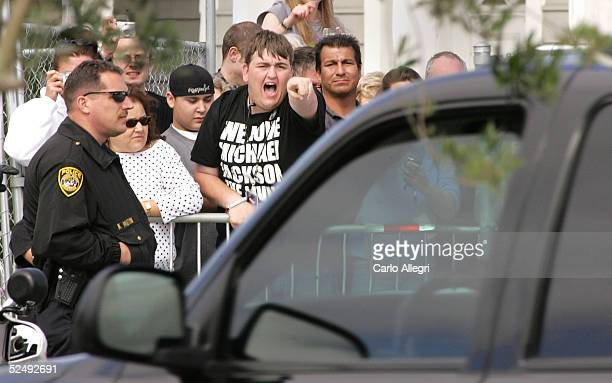 Michael Jackson supporter BJ Hickman yells his support as an SUV carrying Jackson departs the Santa Maria Superior Court during the fifth week of his...