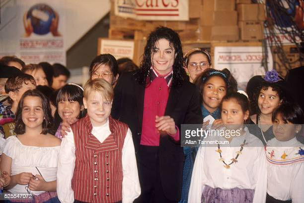 Michael Jackson the 'King of Pop' is surrounded by multicultural children at JFK as relief supplies are loaded onto a plane destined to aid besieged...